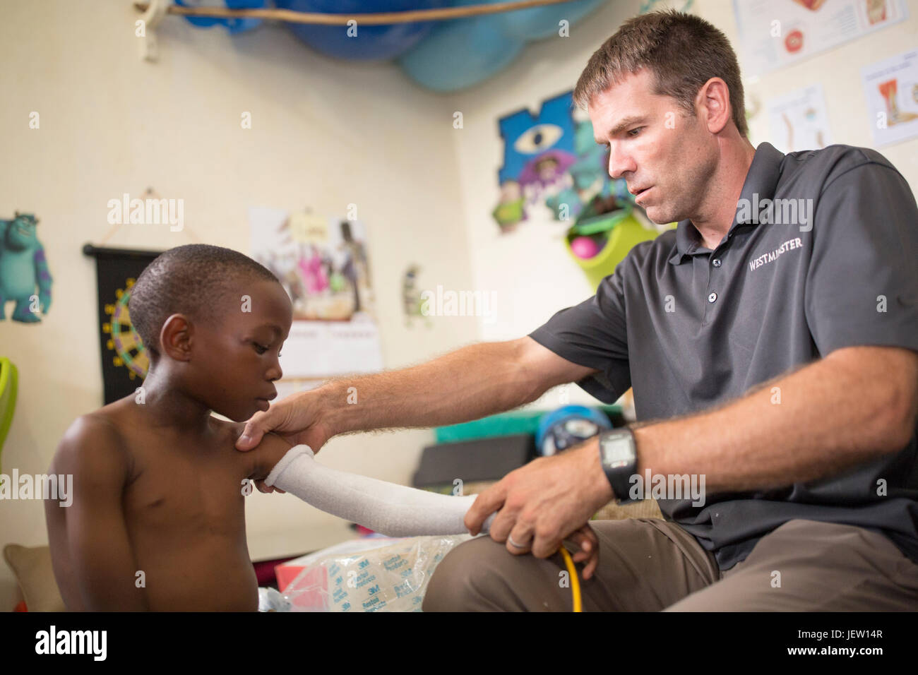 An expat physical therapist fits a boy with a cast in Bundibugyo, Uganda. - Stock Image