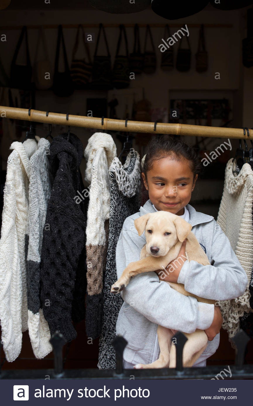 Clutching a puppy, a young girl pauses by a store selling hand knit woolen wares. - Stock Image