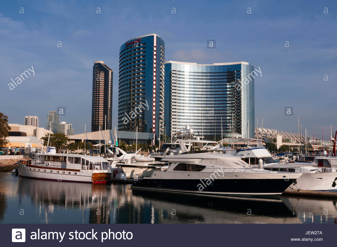 Boats anchored in a harbor marina within walking distance of modern hotels. - Stock Image