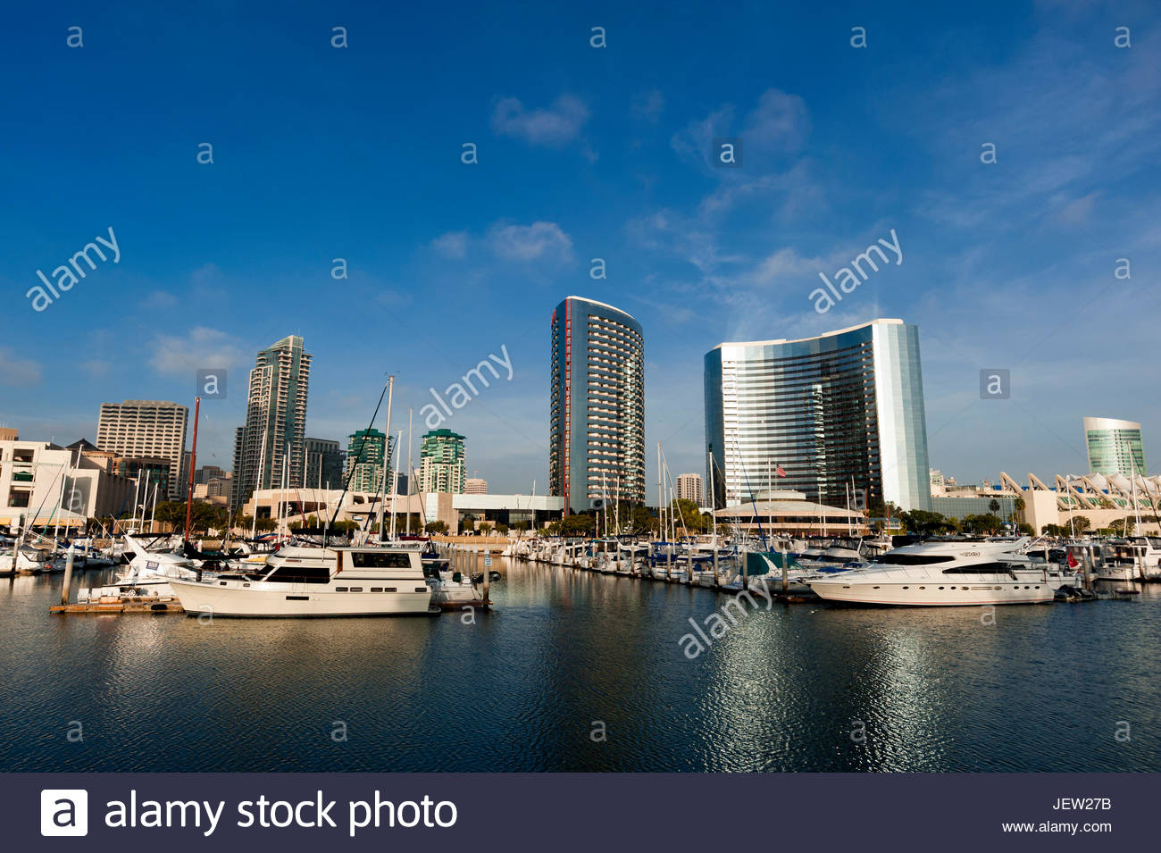 A view boats anchored in a marina and the San Diego skyline. - Stock Image