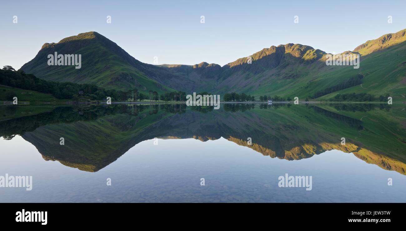 Still water reflections of Buttermere. The image was taken on a still summers morning - Stock Image