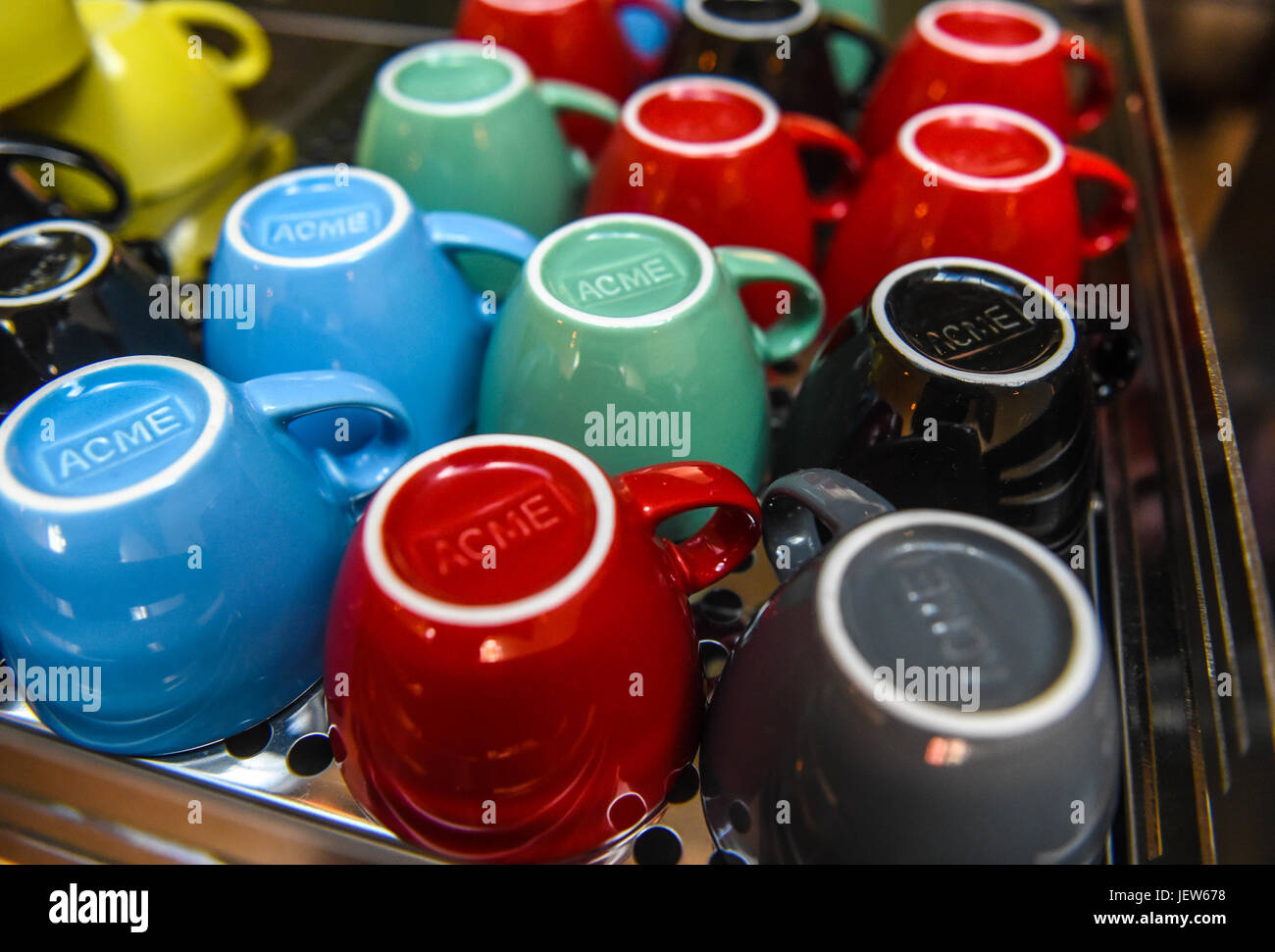 Copyrighted Image by Paul Slater/PSI -  Coloured Coffee mugs on display, drying. - Stock Image
