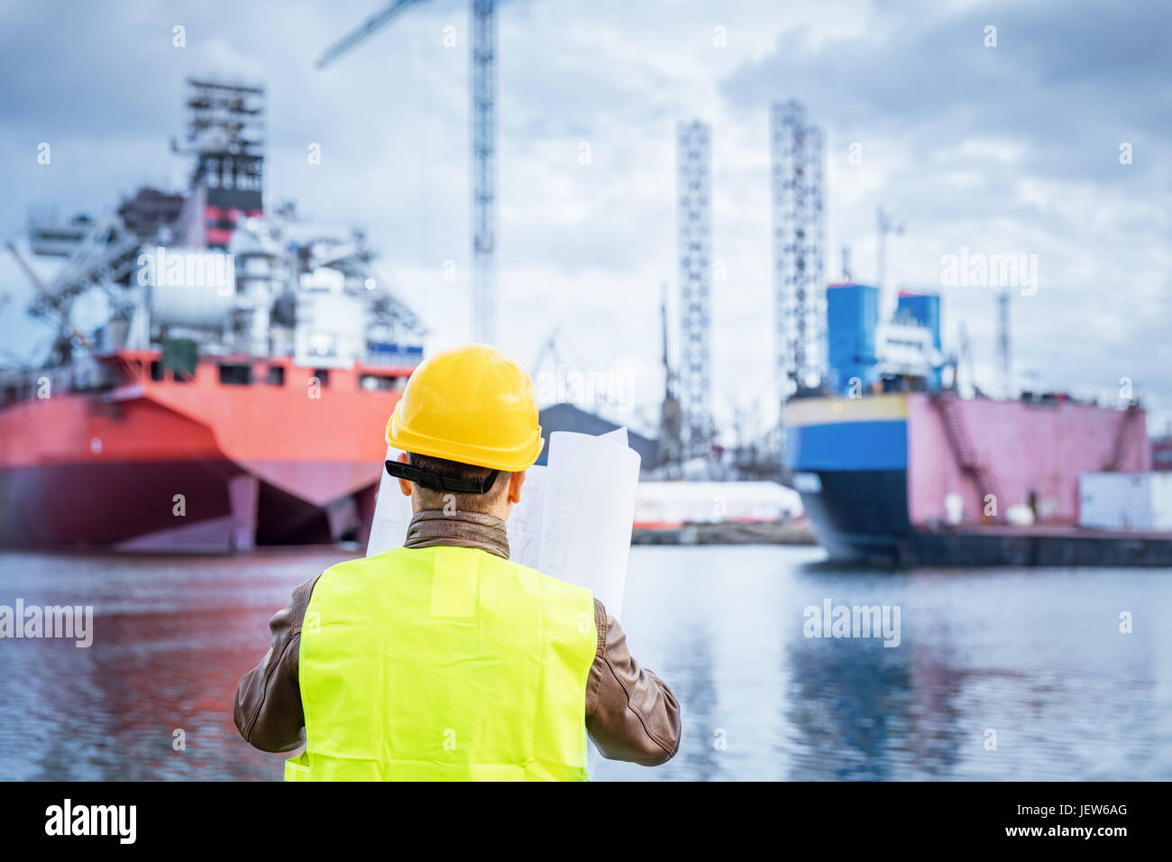 Shipbuilding engineer checking documents and plans of construction at the dockside in a port. Wearing safety helmet - Stock Image