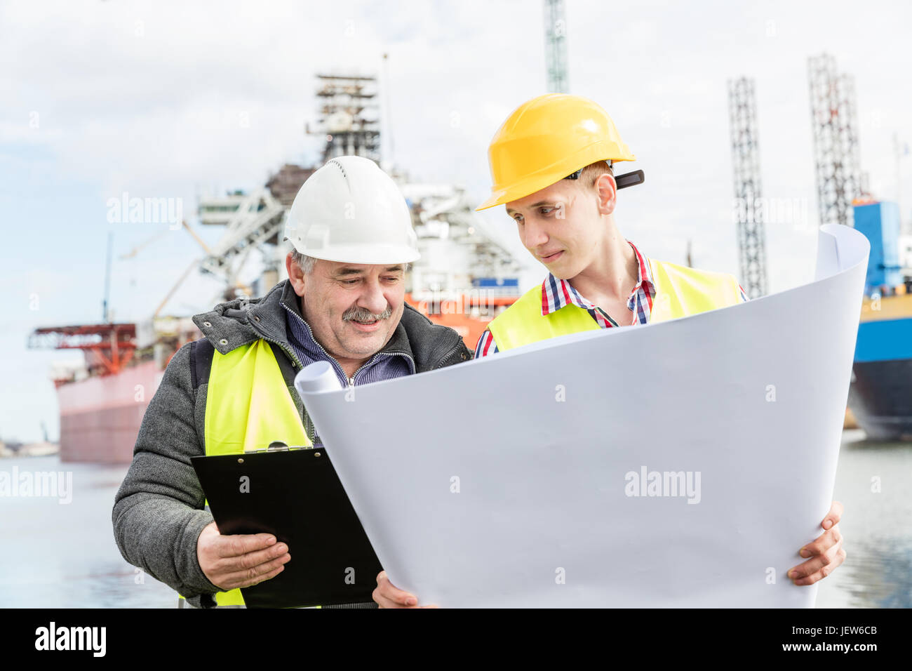 Shipbuilding engineer discusses documents with a student. Experienced worker wearing white safety helmet explains - Stock Image