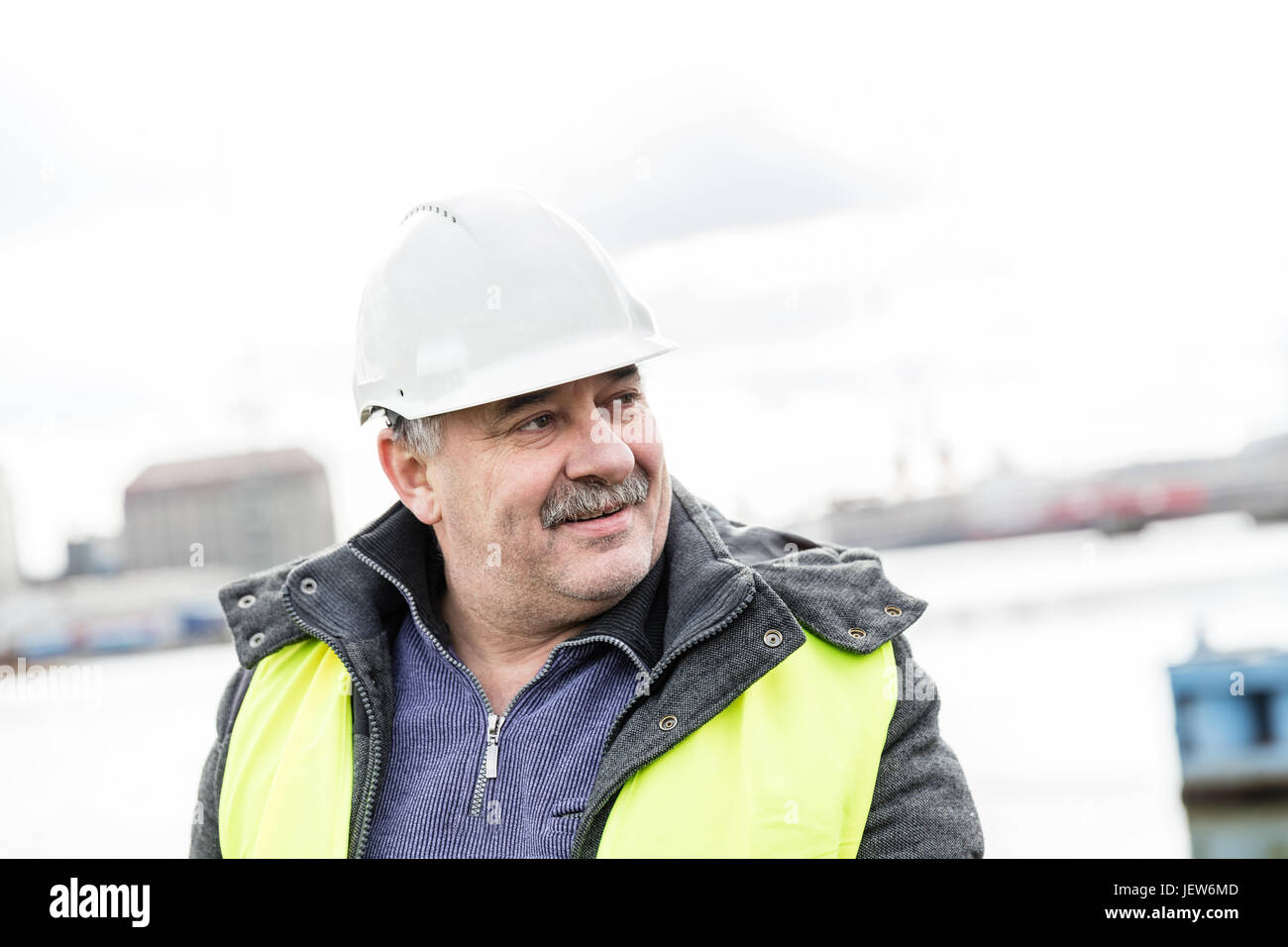 Senior engineer builder at the construction site in a port. Wearing safety helmet and yellow vest. - Stock Image