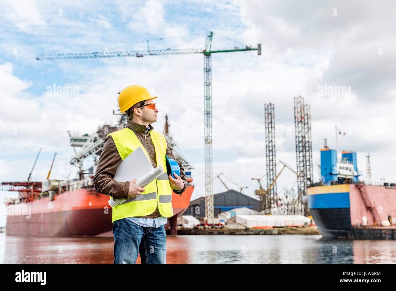 Shipbuilding engineer stands at the dockside in a port. Wearing safety helmet, yellow vest and safety glasses. Shipbuilding - Stock Image