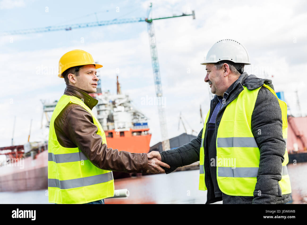 Shipbuilding deal concluded by a handshake of two engineers. Company contract - Stock Image