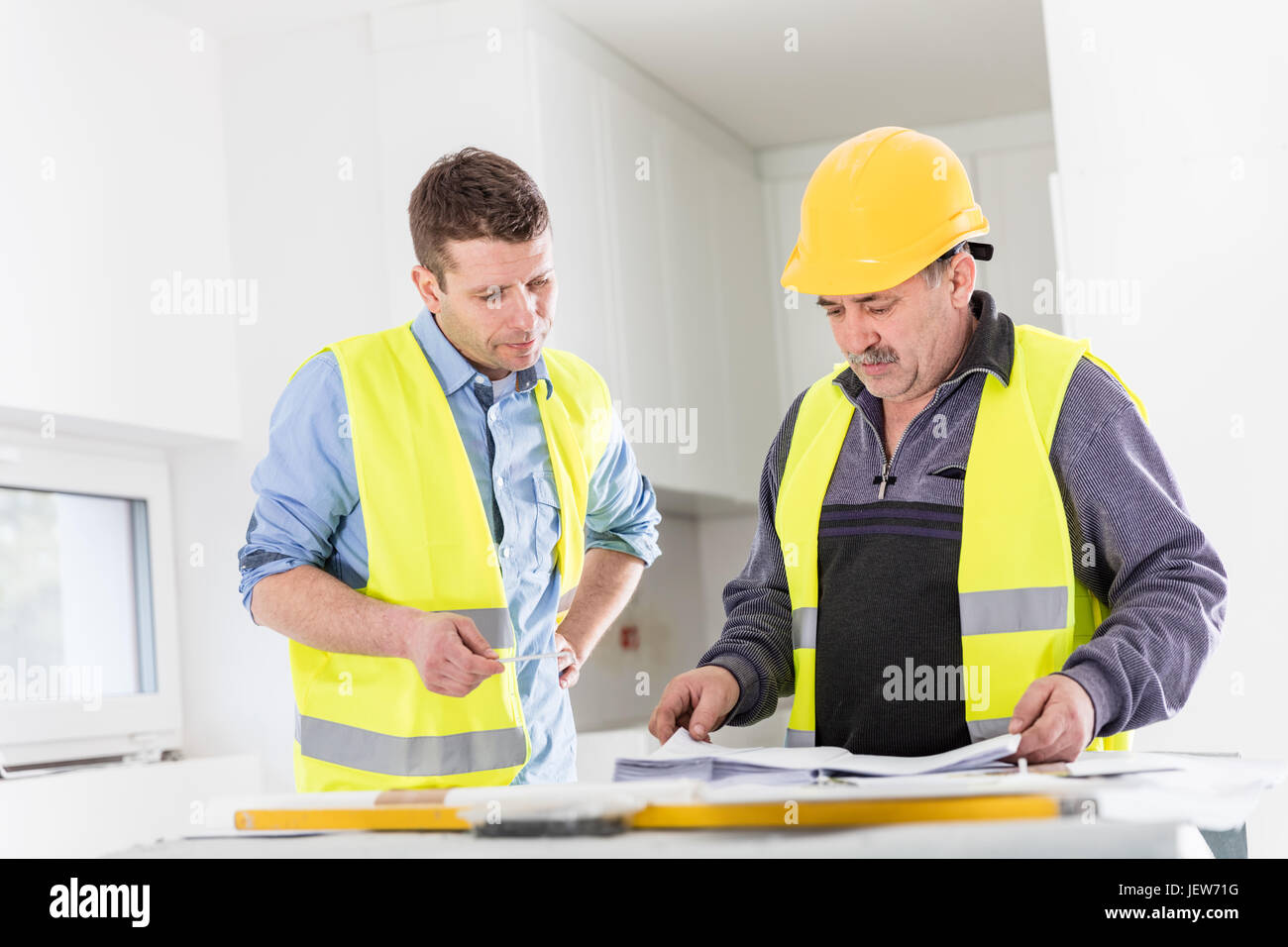 Architect and construction engineer indoor meeting. Building experts cooperation and project analysis. Real estate - Stock Image