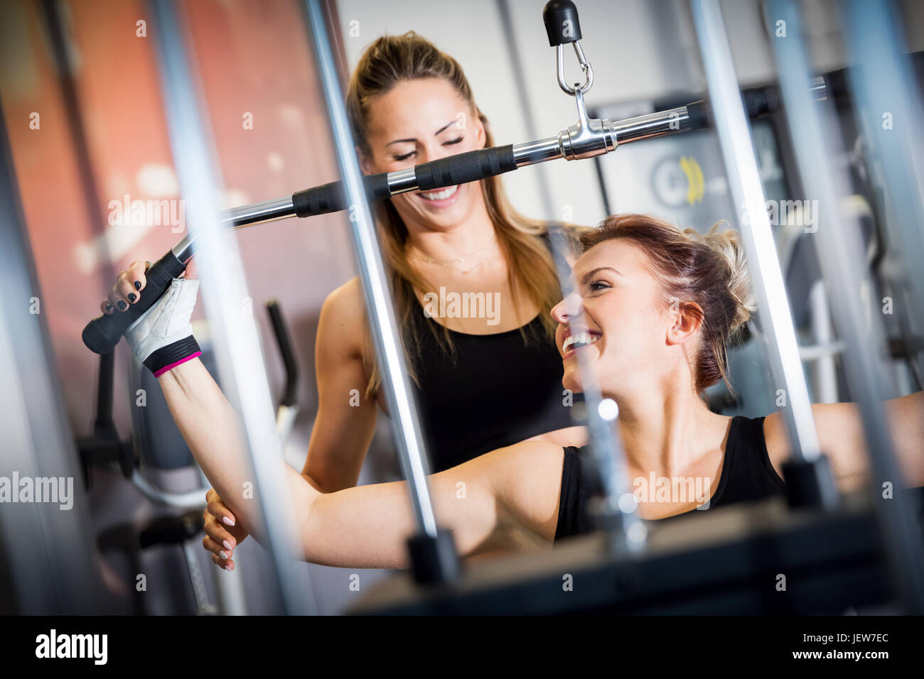 Personal trainer helps with gym equipment workout. Two attractive women training, building strength. Sport concept. - Stock Image