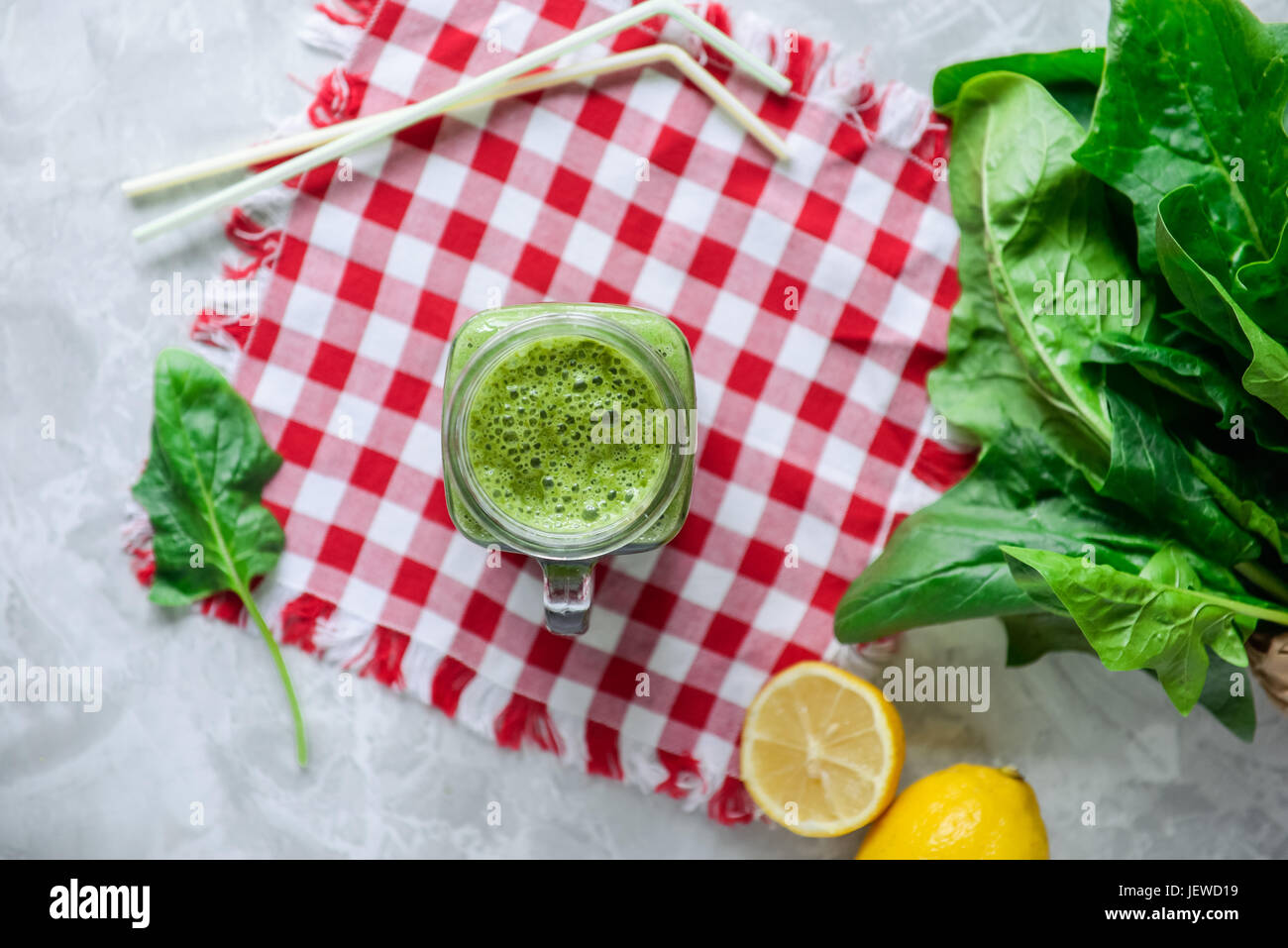 Top view Healthy green spinach smoothie in a jar mug with ingredients on the checkered napkin on the white marble Stock Photo