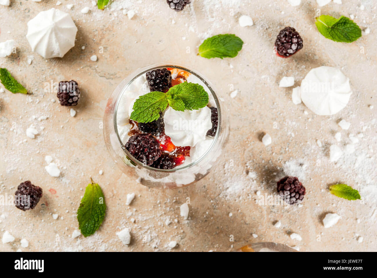 Traditional English dessert. Eton mess - whipped cream, meringue, fresh blackberries, sauce and caramel. In serving - Stock Image