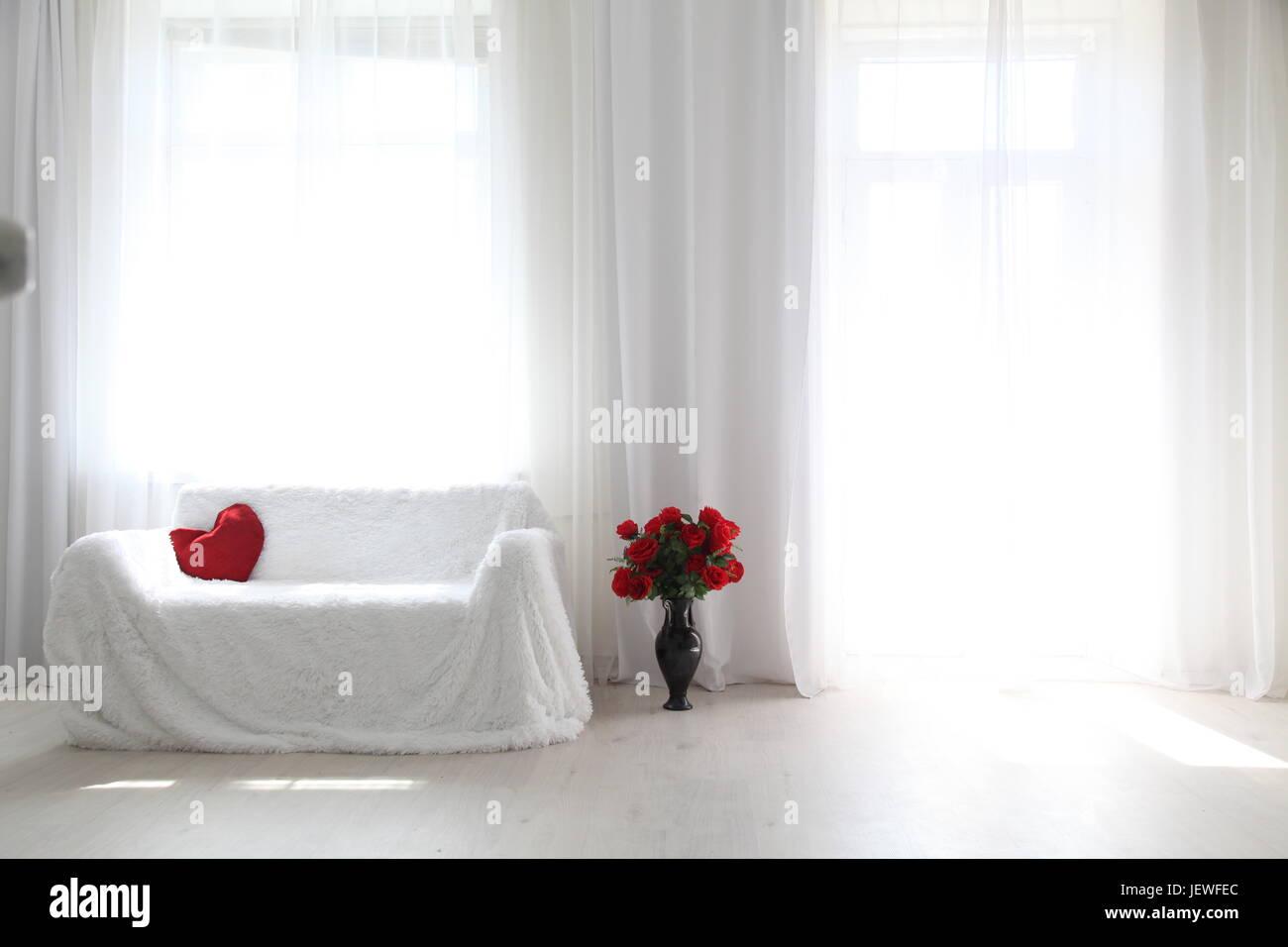Interior white room sofa flowers light from the window Stock Photo
