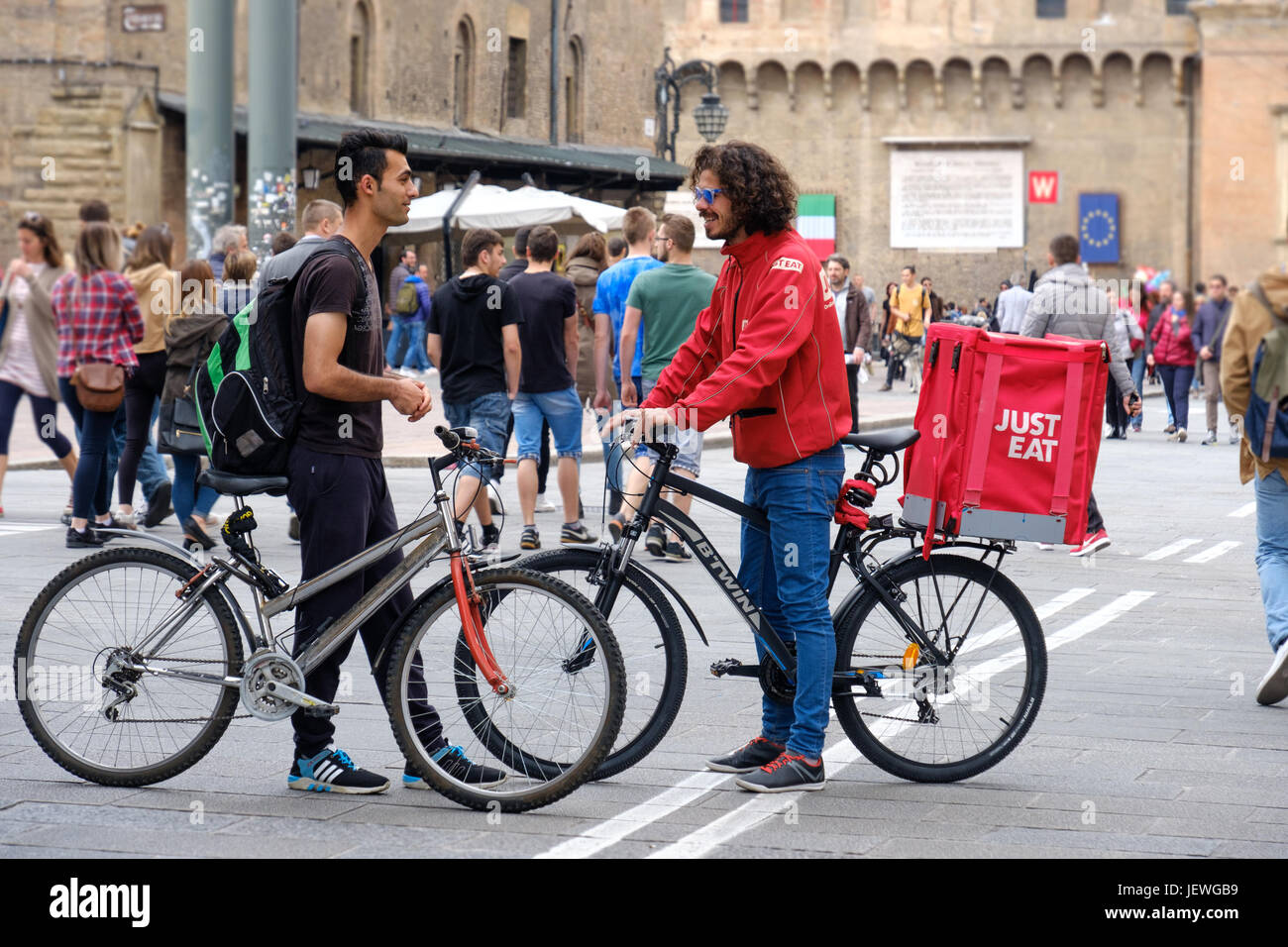 Bologna, Italy, 1 May 2017 - A Just Eat bike deliver courier speak with another cyclist in the Bologna's main - Stock Image