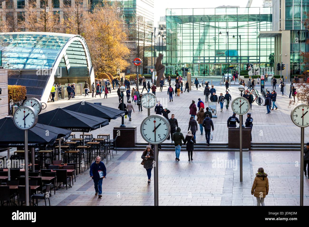 People walking in Reuters Plaza and Jubilee Plaza in Canary Wharf and public installation 'Six Public Clocks' - Stock Image