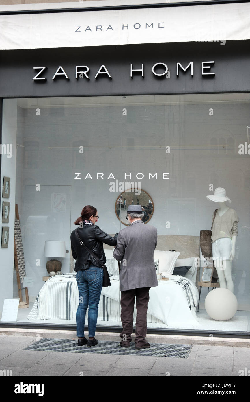 Bologna, Italy, 1 May 2017 - an old man and a woman look at the showcase of the Zara Home furnishing store in Bologna - Stock Image
