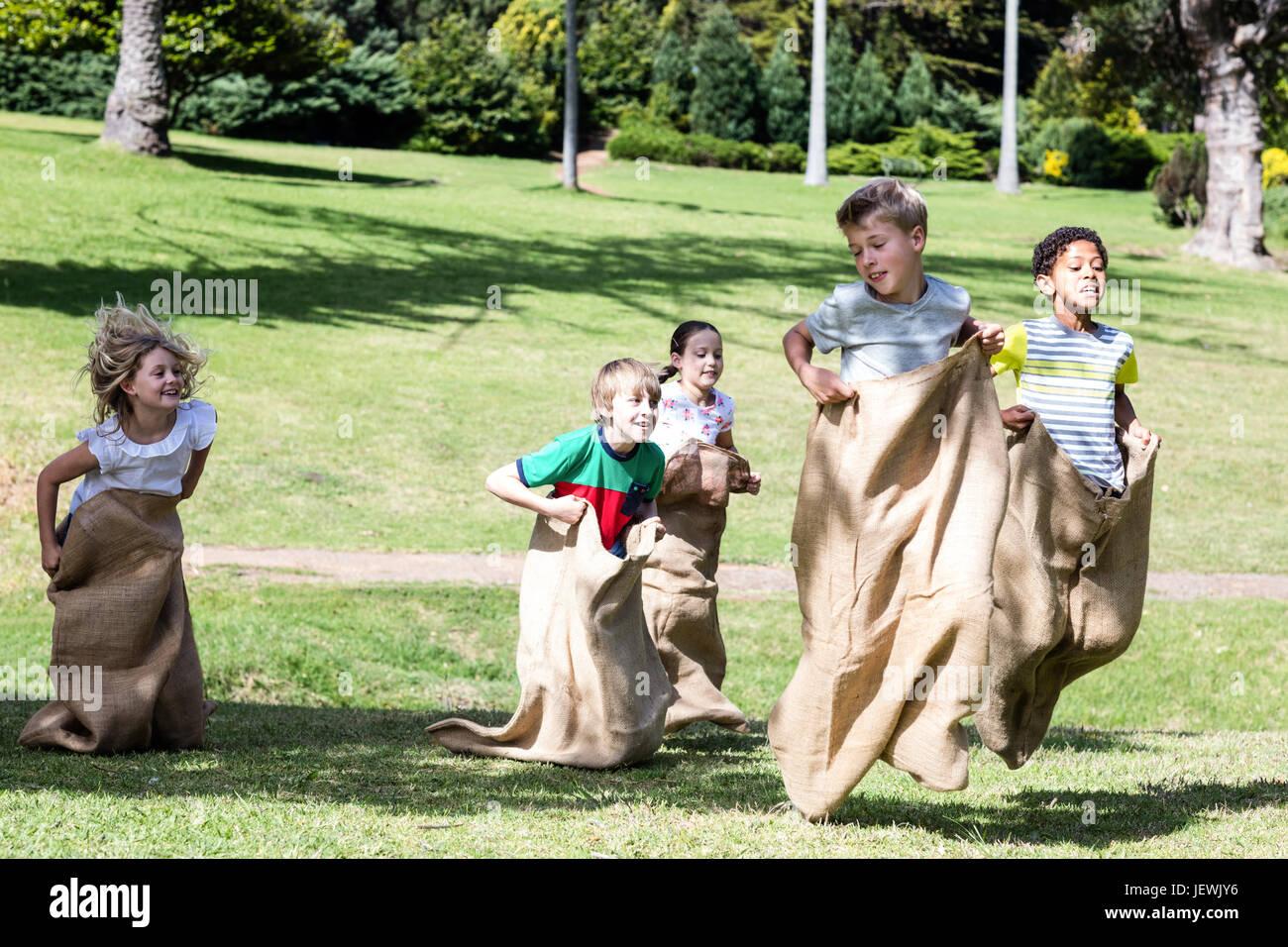 Children having a sack race in park - Stock Image