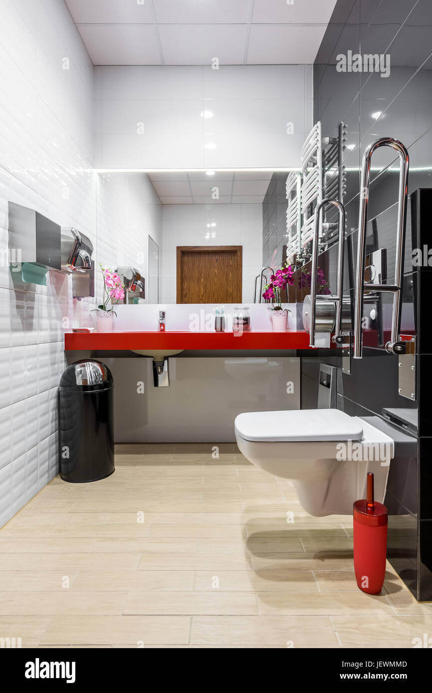 Black and white modern bathroom with toilet, red countertop and ...