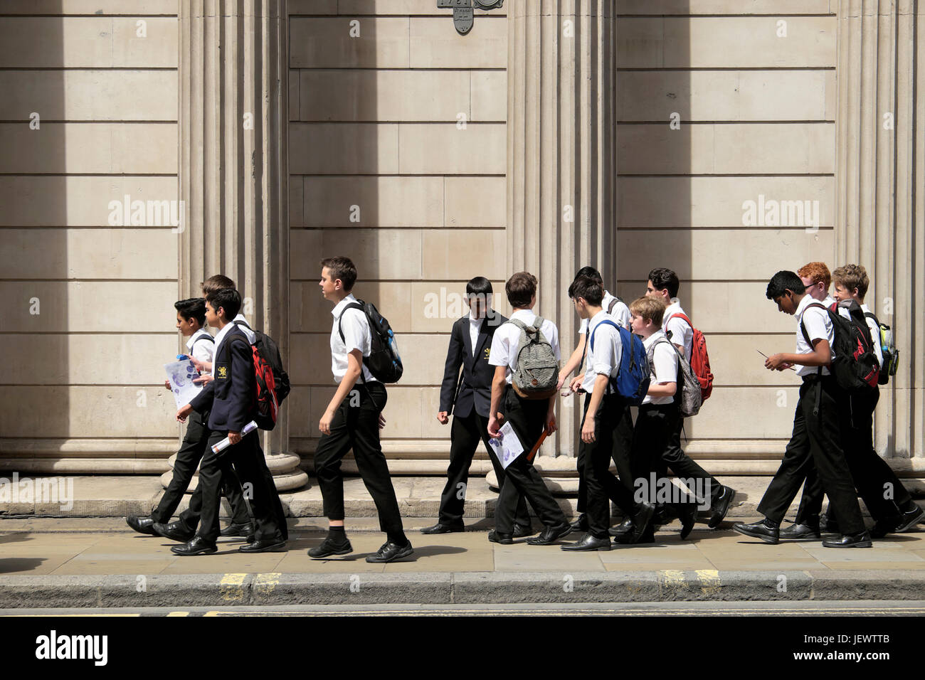 School boys walking along the street outside the Bank of England Museum on Threadneedle Street in financial district - Stock Image