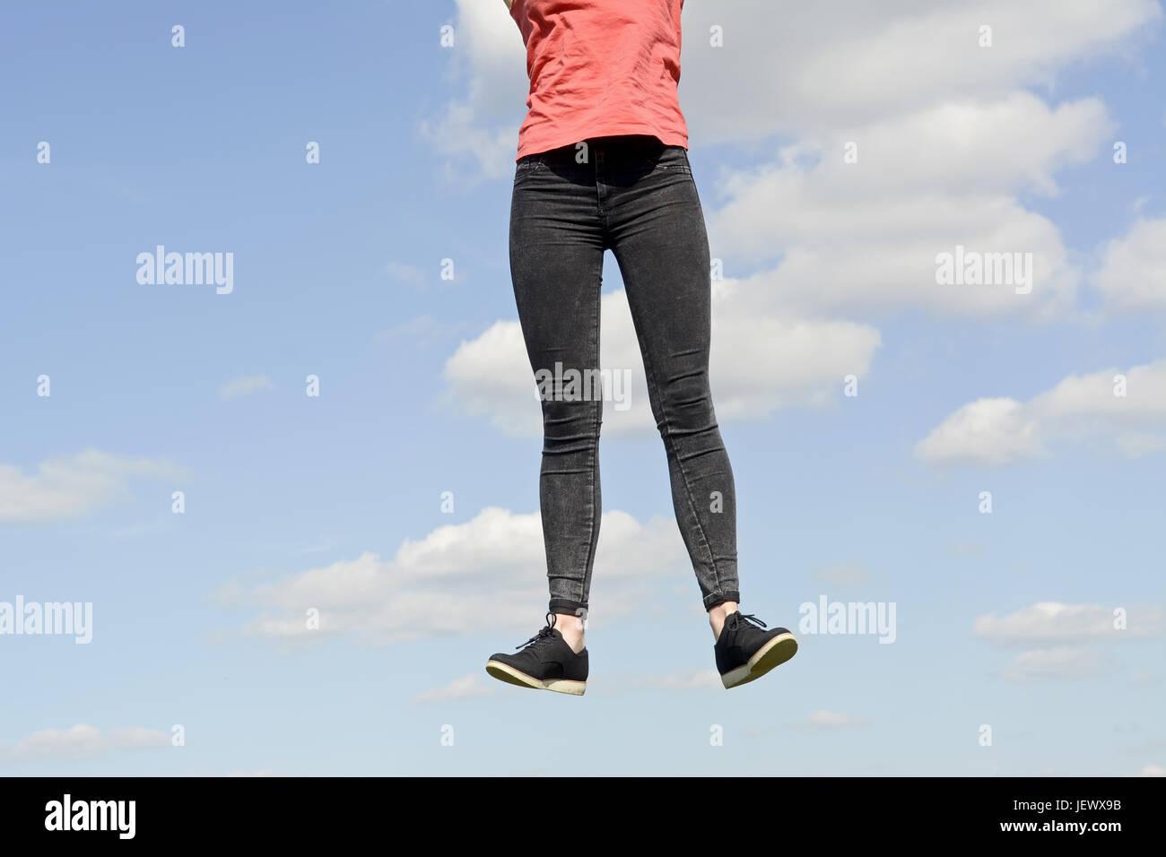 joyful young woman leaping - Stock Image