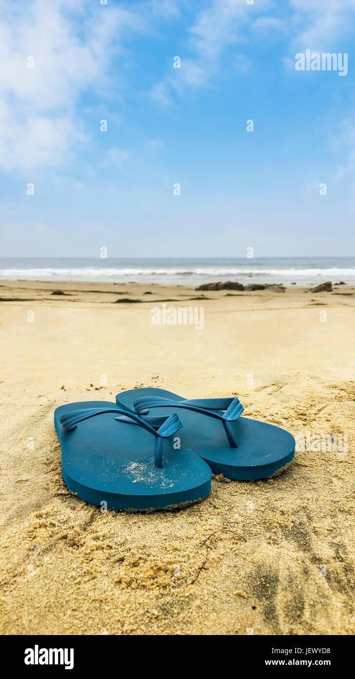 89966bb62ec2f4 Blue sandals — flip flops overlooking beach shoreline. - Stock Image