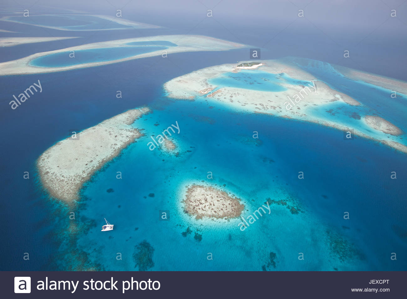 An aerial view of a catamaran anchored near an atoll in the Maldive Islands. - Stock Image