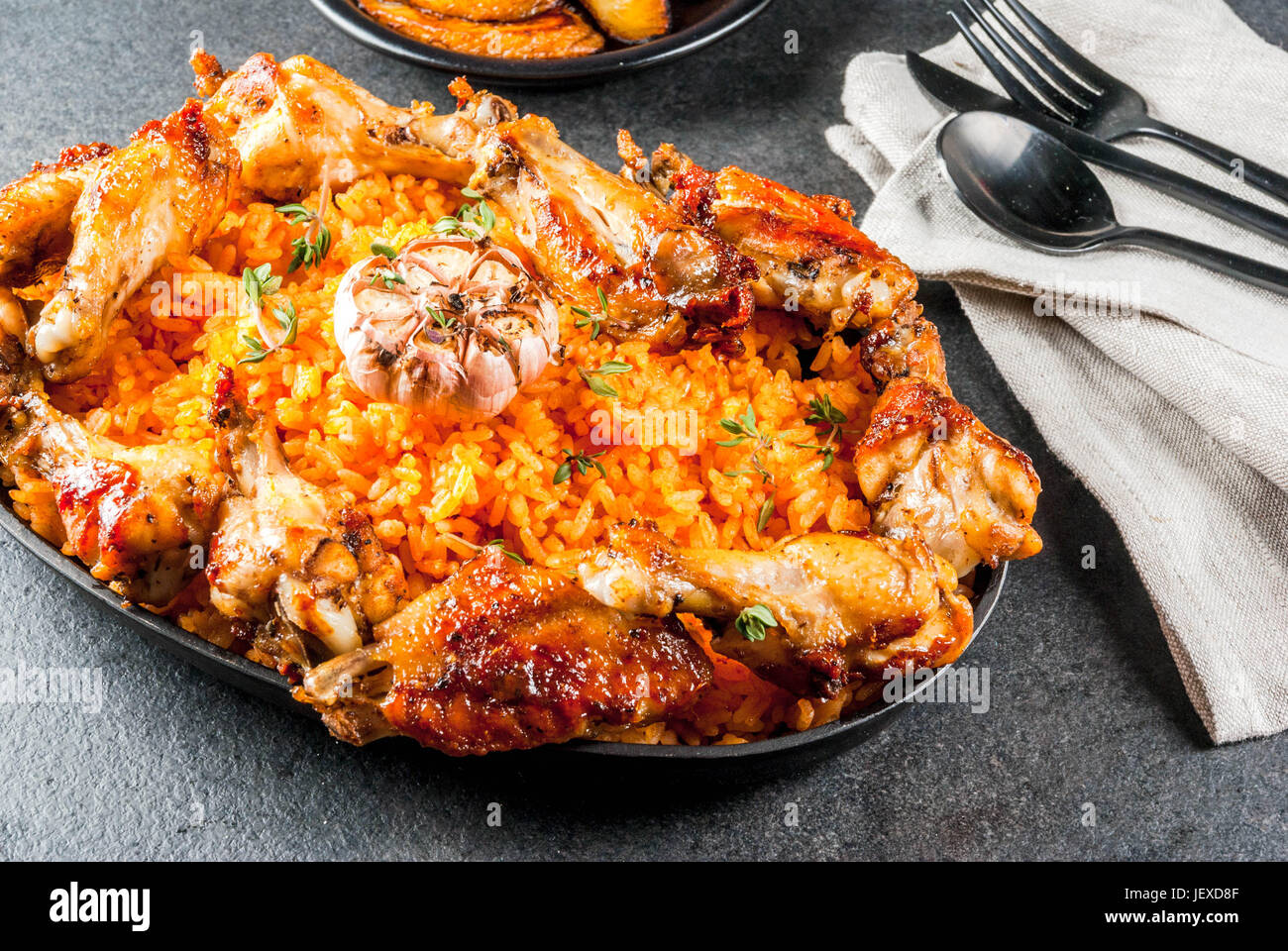 West African national cuisine. Jollof rice with grilled chicken wings and fried bananas plantains.On gray stone - Stock Image