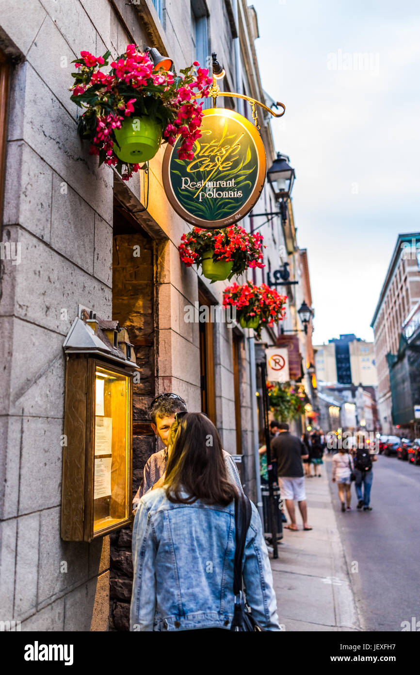 Montreal, Canada - May 27, 2017: Old town area with people under restaurant sign reading menu by street in evening - Stock Image