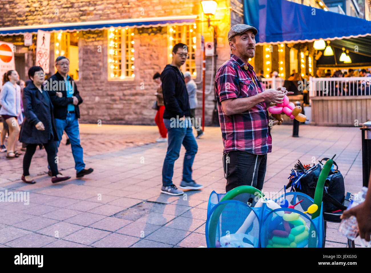 Montreal, Canada - May 27, 2017: Old town area with people walking up street in evening and balloon man in Quebec - Stock Image