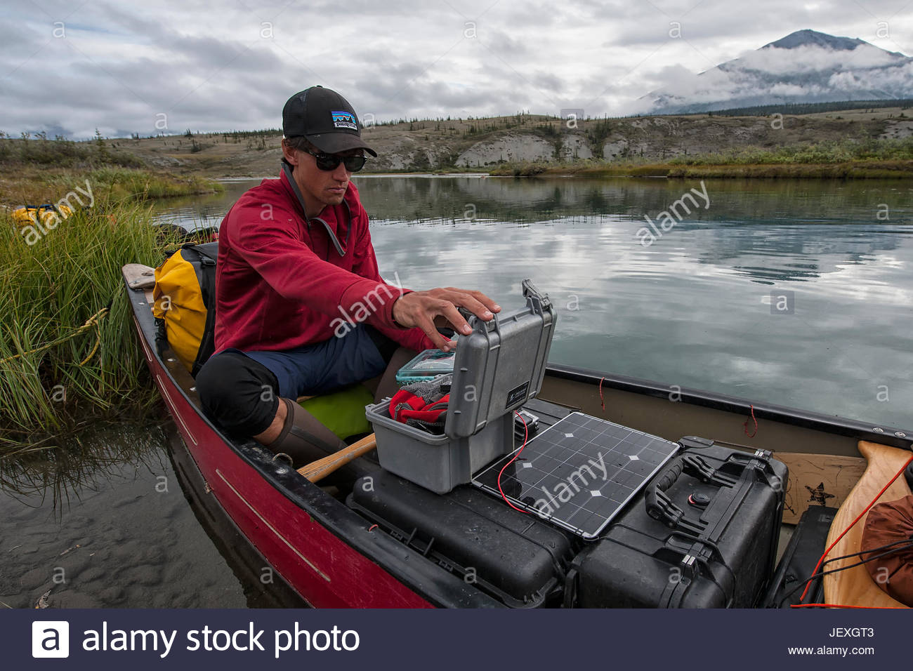 Videographer filming on the Wind River. Also, charging batteries using a solar charging system from our sponsors - Stock Image