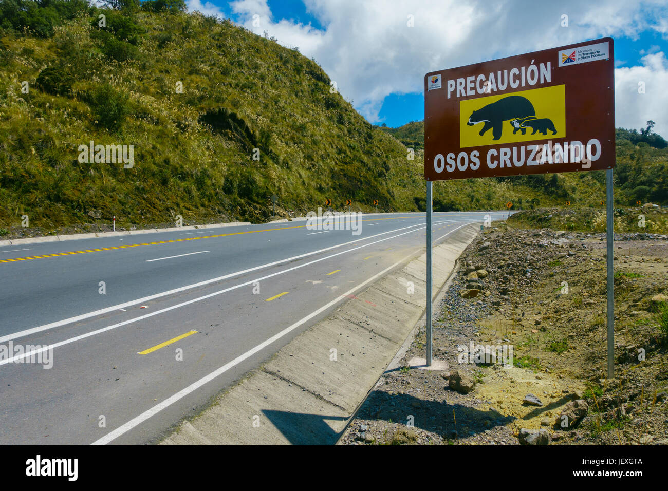 QUITO, ECUADOR - AUGUST 8, 2014: Informative sign to aware the crossing of bears in Papallacta, in a beautiful landscape Stock Photo