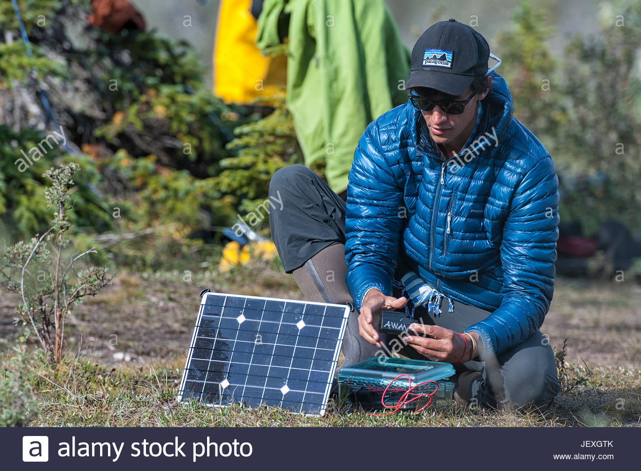 Videographer charging batteries using a solar charging system from our sponsors at Voltaic Systems. The solar charger - Stock Image
