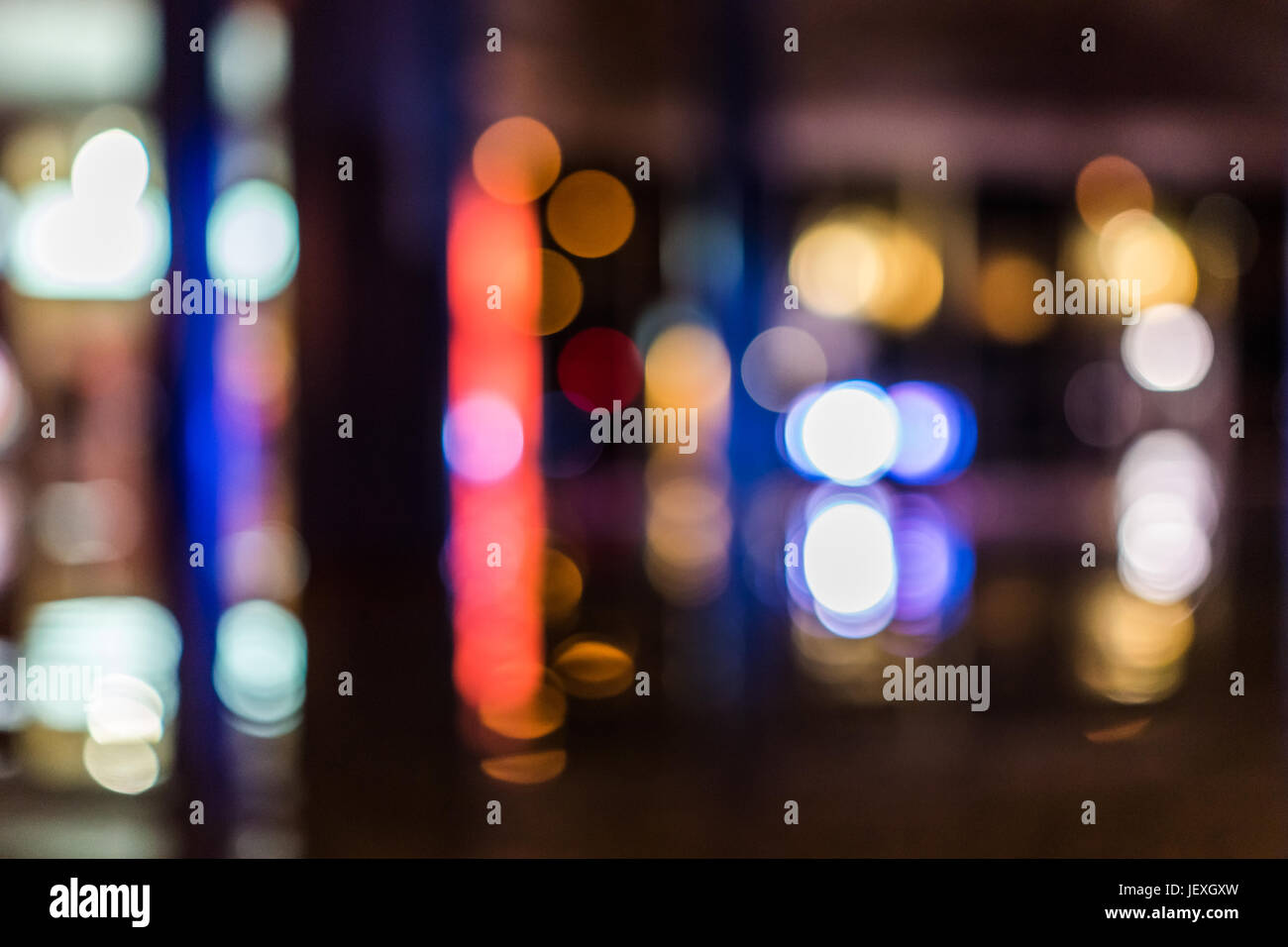 Bokeh circles of fountain with reflection during dark evening night - Stock Image