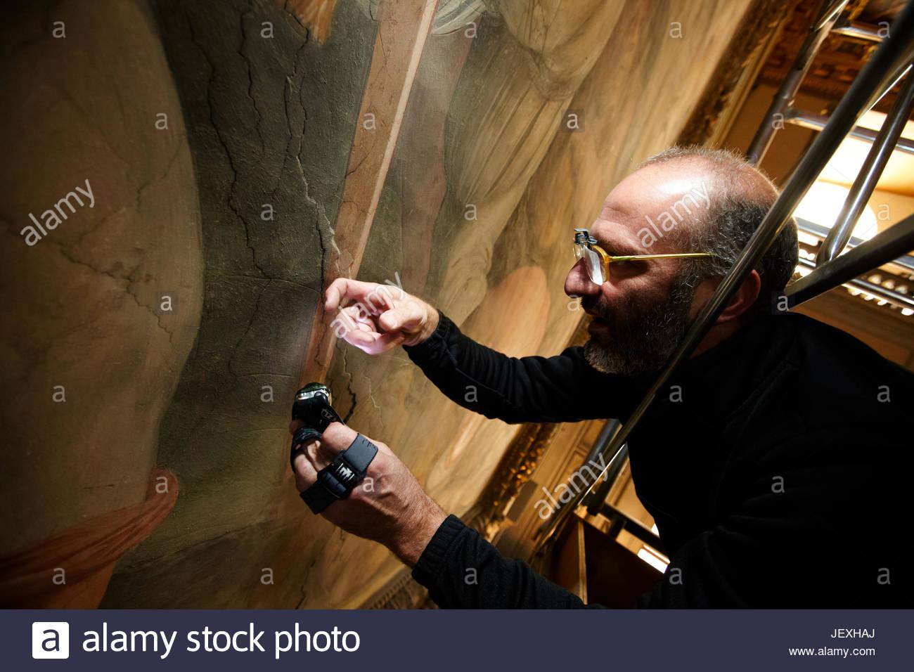Art restorer Alberto Felici, of the Opificio delle Pietre dure, tests Giorgio Vasari's mural on the east wall - Stock Image