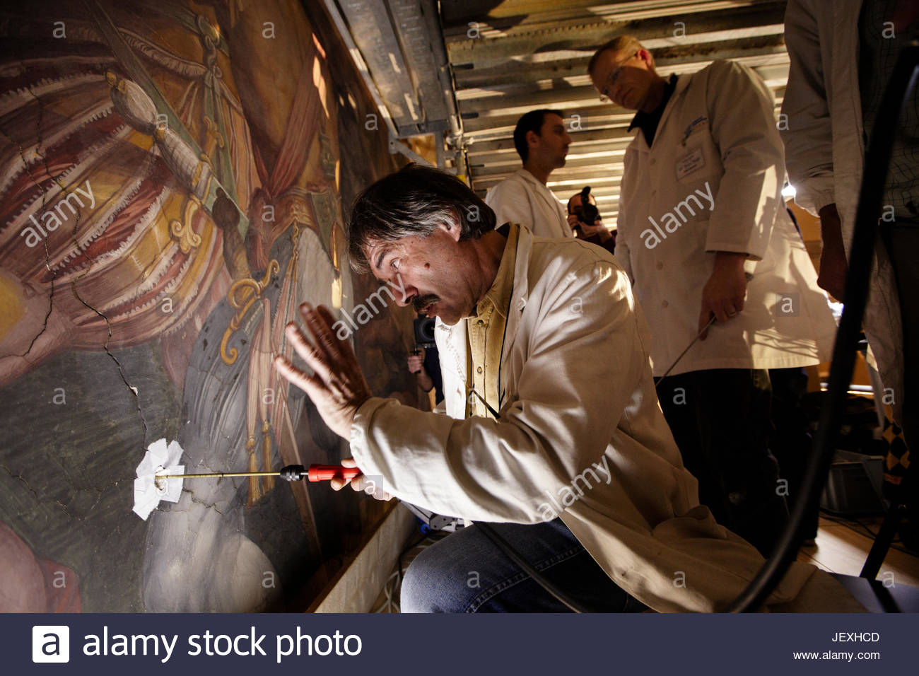 Restorers from the Opificio delle Pietre Dure drill through holes made available while restoring a Giorgio Vasari - Stock Image