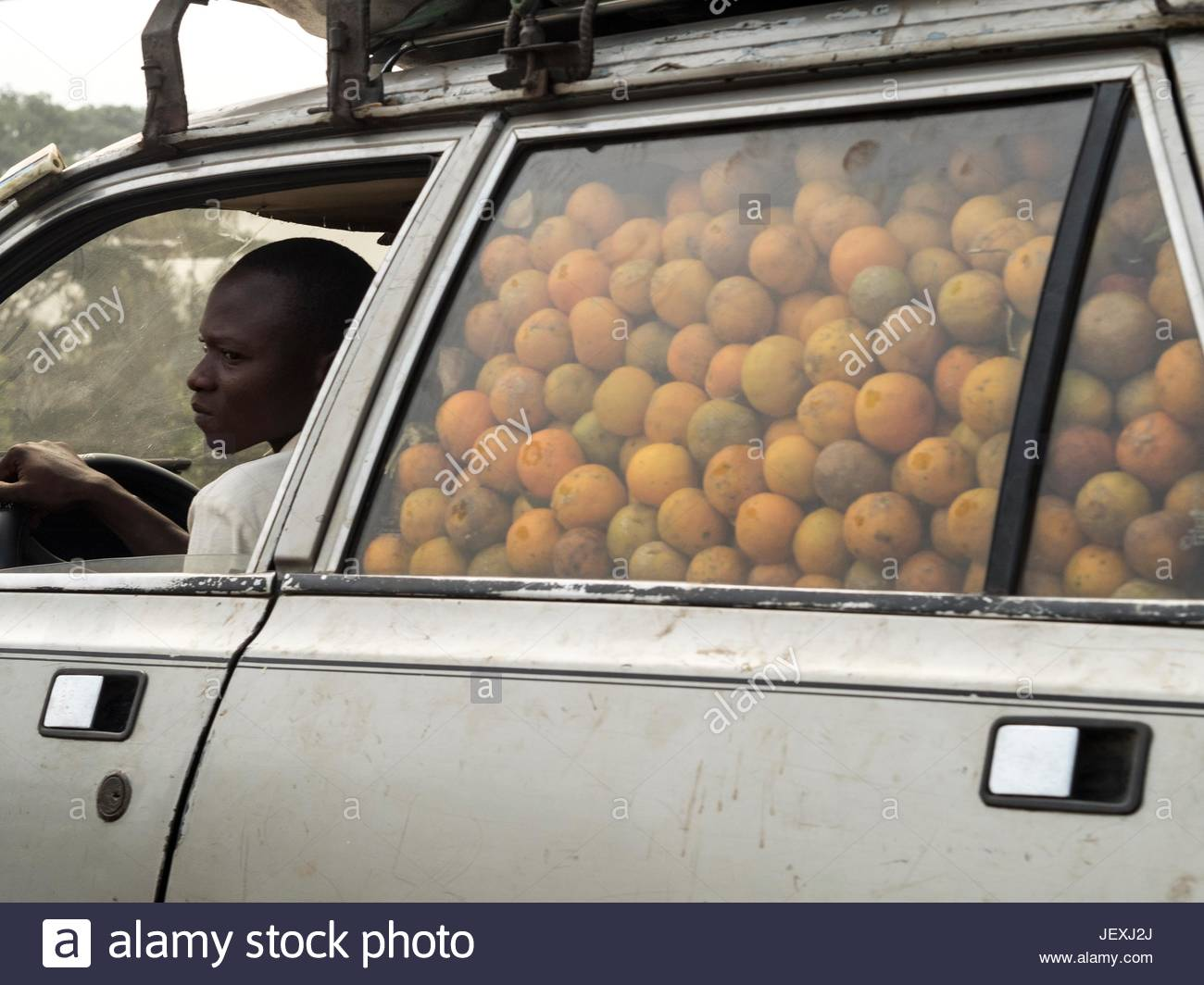 A man drives a car filled with oranges. - Stock Image