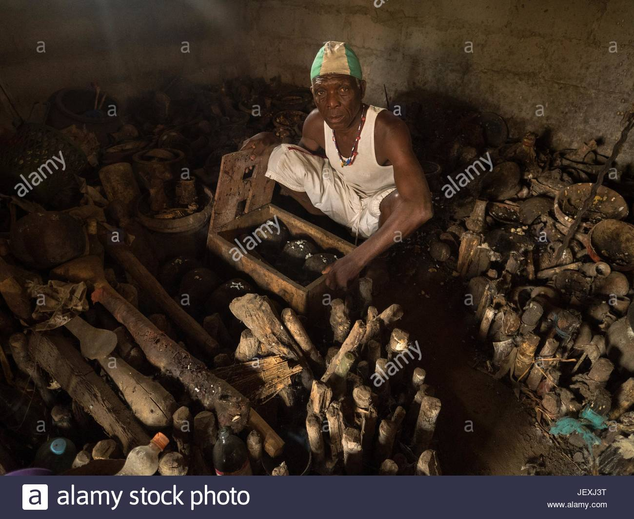 A houngan or voodoo priest sits in front of human skulls and