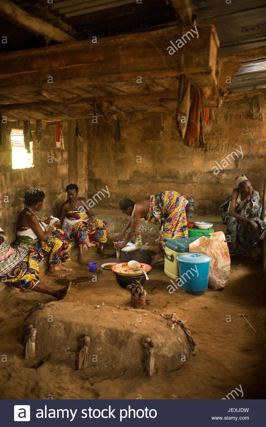 Women prepare a voodoo dinner by three coffins and a tomb with human bones near the town of Bopa during the voodoo - Stock Image