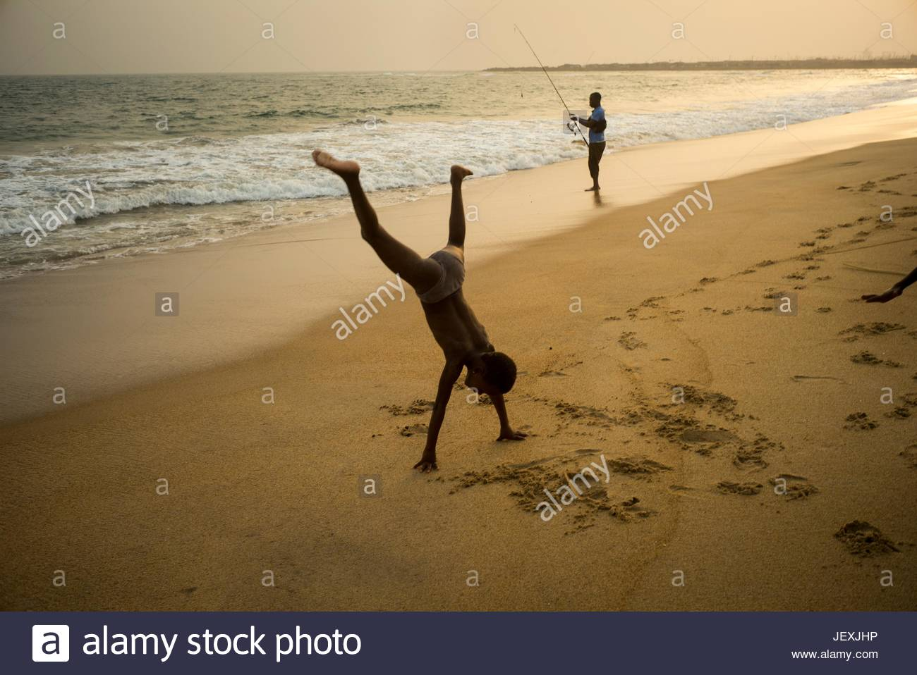 A boy does a cartwheel on the beach near a fisherman along the water's edge. - Stock Image