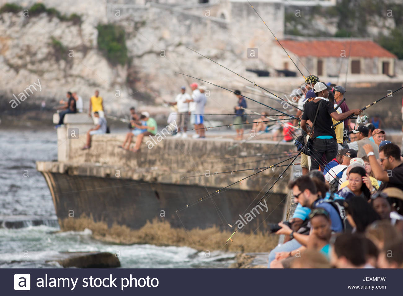 Tourists sightsee while locals fish off the stone wall of the Malecon in Havana, Cuba. - Stock Image