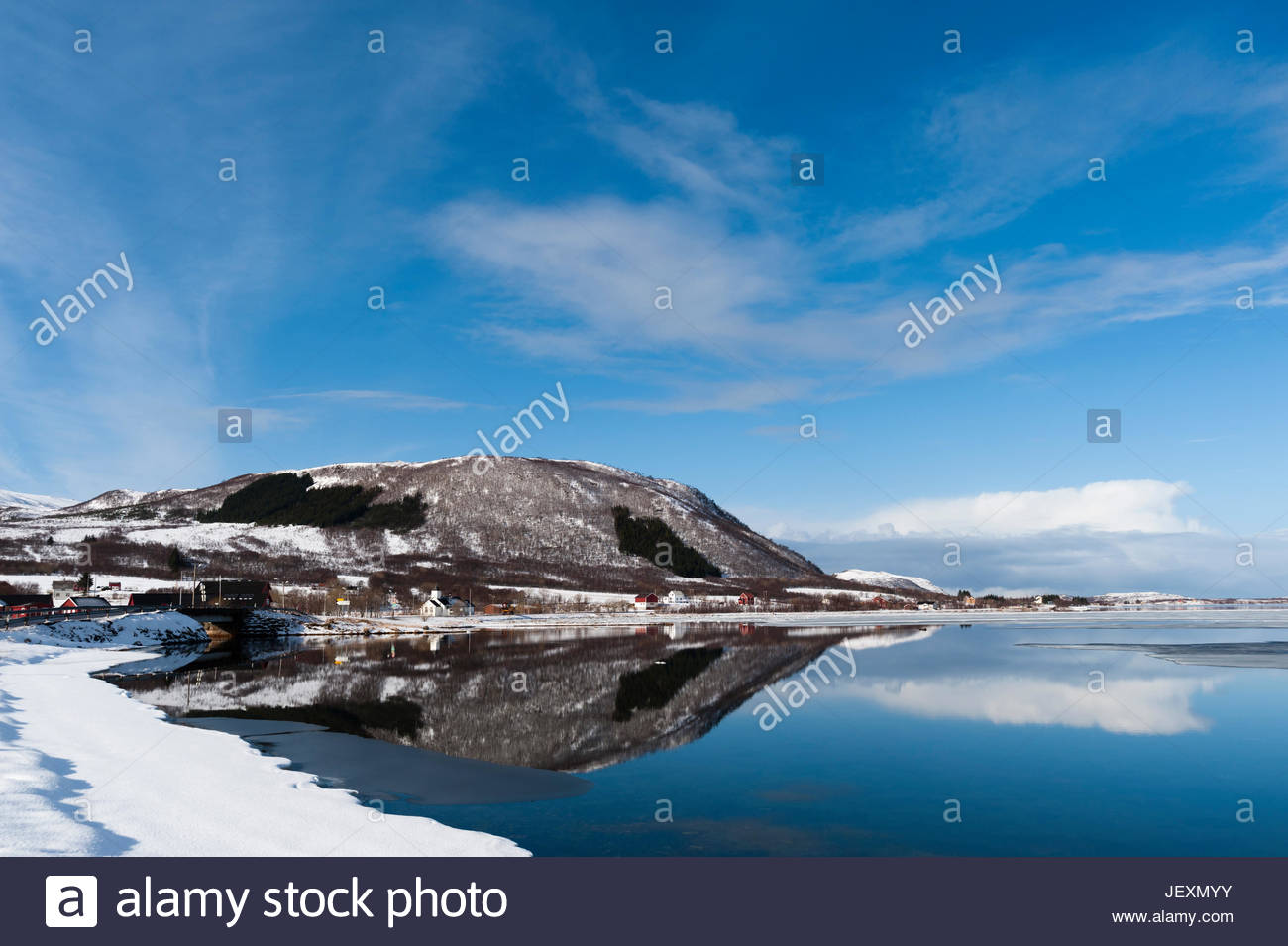 The small coastal village of Knutstad, with snowy shores and blue skies. - Stock Image