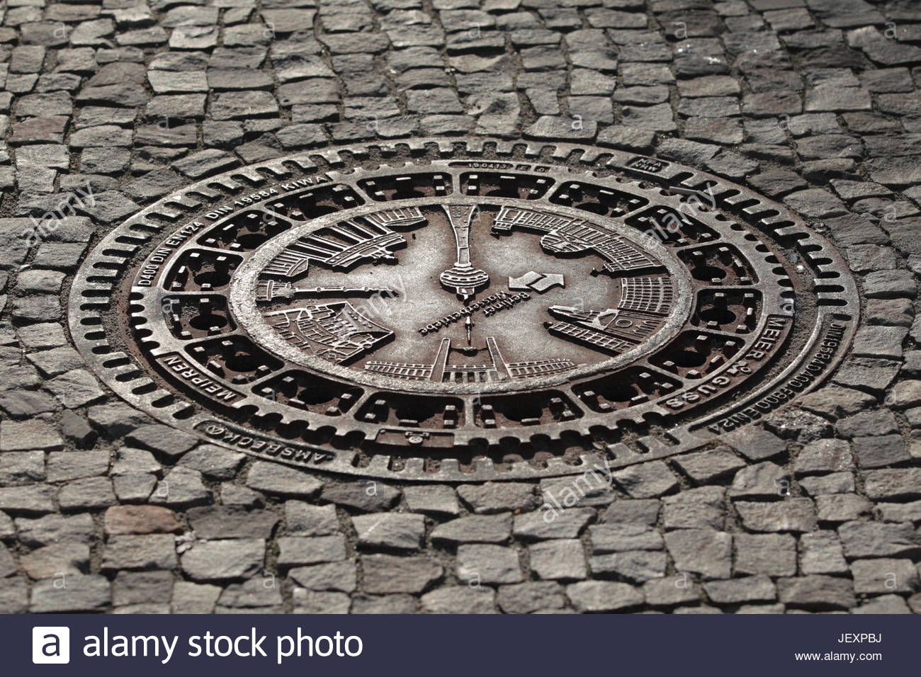 An ornate manhole cover in a cobblestone street. - Stock Image