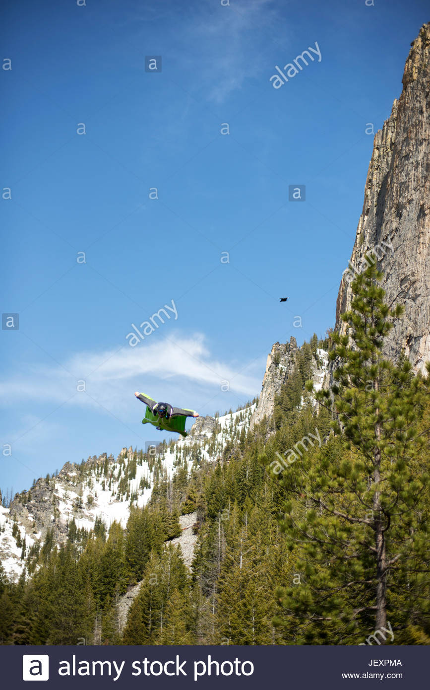 Two wingsuit pilots fly in close proximity to a mountain. - Stock Image