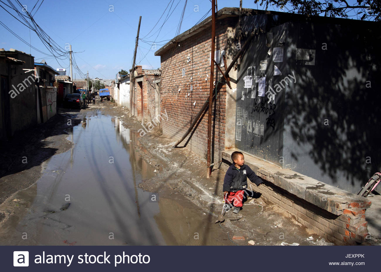 A child playing on a small road in a migrant worker village on the outskirts of Beijing. - Stock Image
