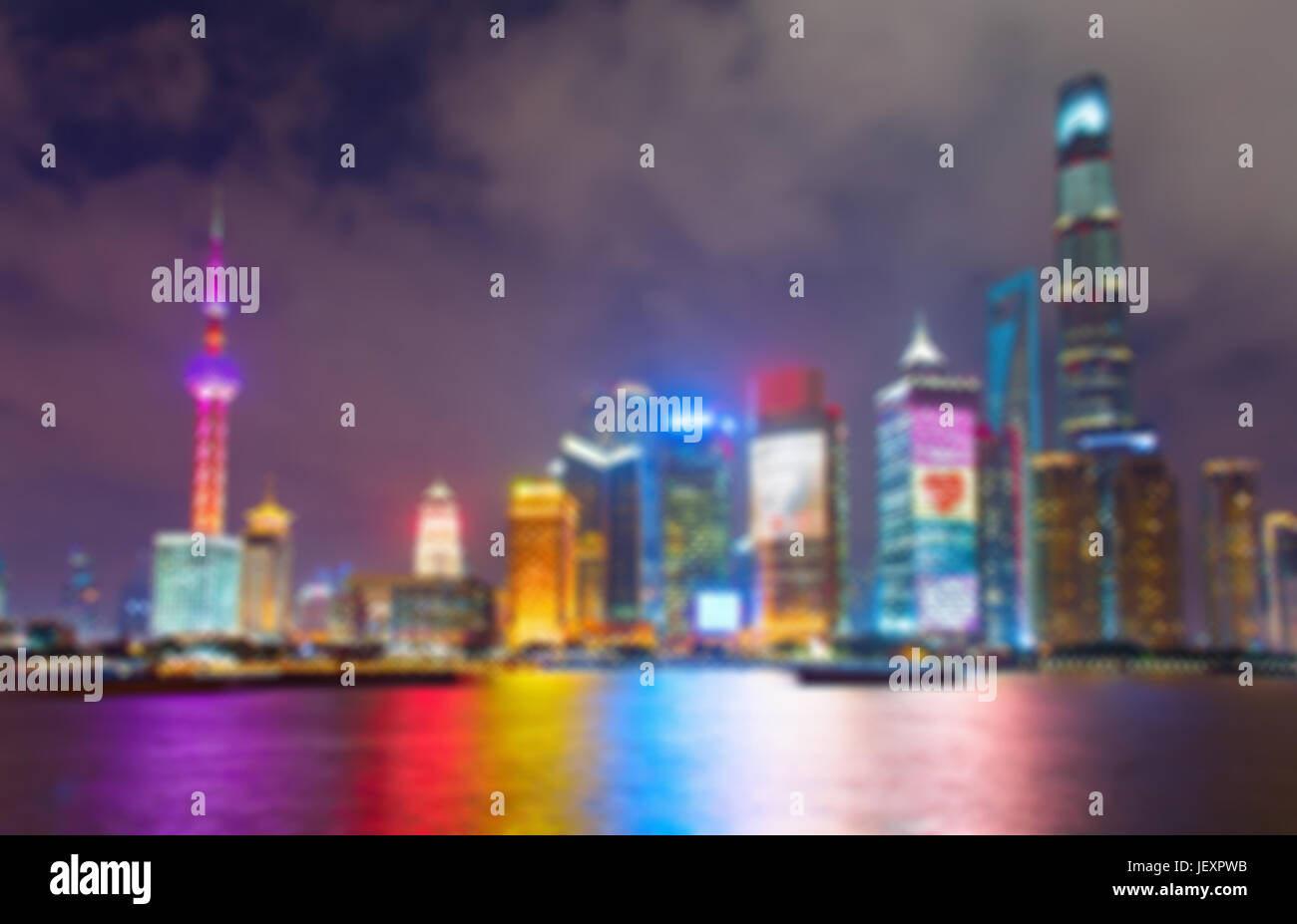 Blurred skyline of Shanghai Downtown at night with reflection in the river - Stock Image