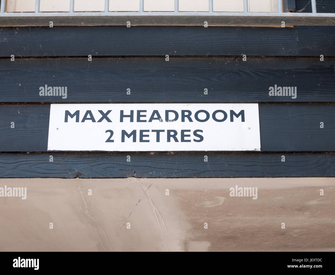 a white and black street sign saying max headroom 2 metres above overhead - Stock Image