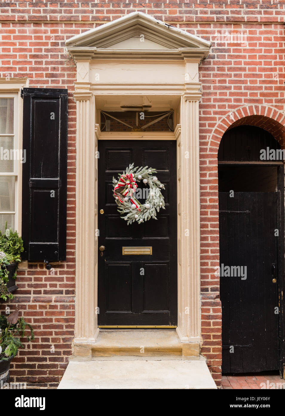 Colonial red doorway in historic Elfreth's Alley in Philadelphia with pediment and  christmas wreath - Stock Image