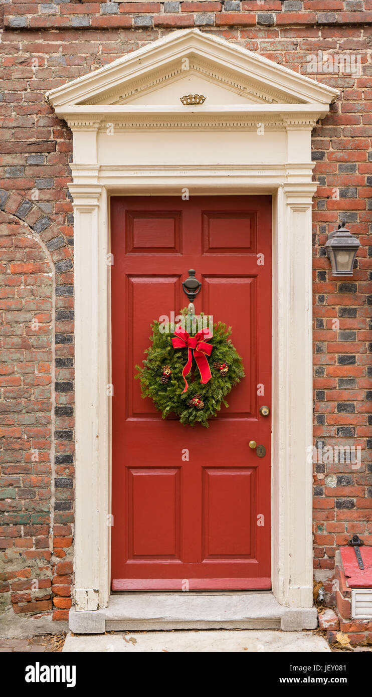 Colonial red doorway in historic Elfreth's Alley in Philadelphia with pediment and  christmas wreath. - Stock Image