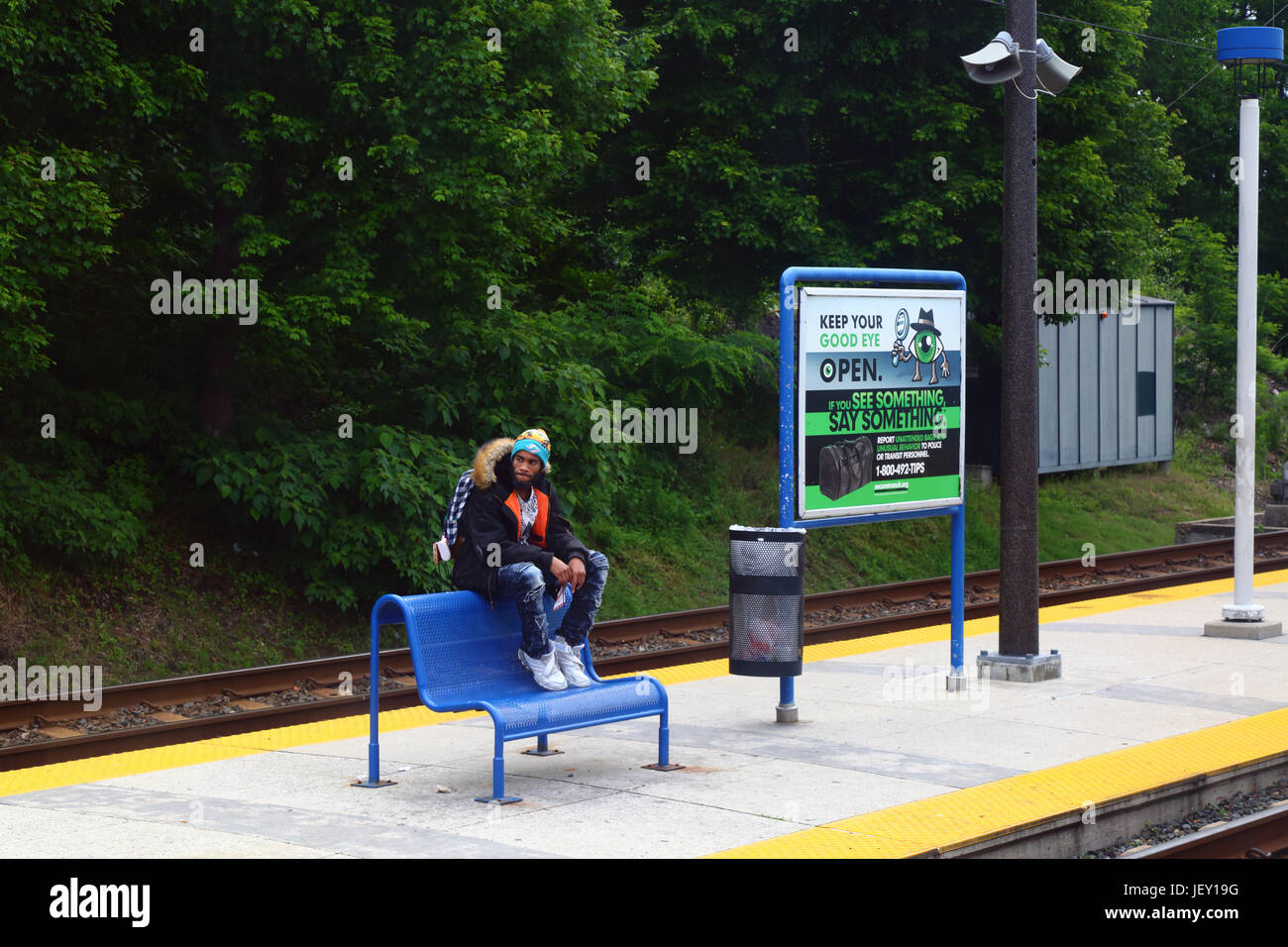 Man sitting on seat next to security billboard on Light Railway station platform, Baltimore, Maryland, USA - Stock Image