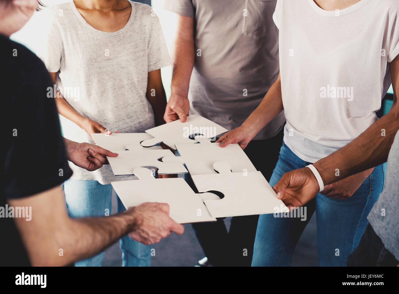 Team of young businessmen combine pieces of puzzle. Concept of integration and partnership - Stock Image