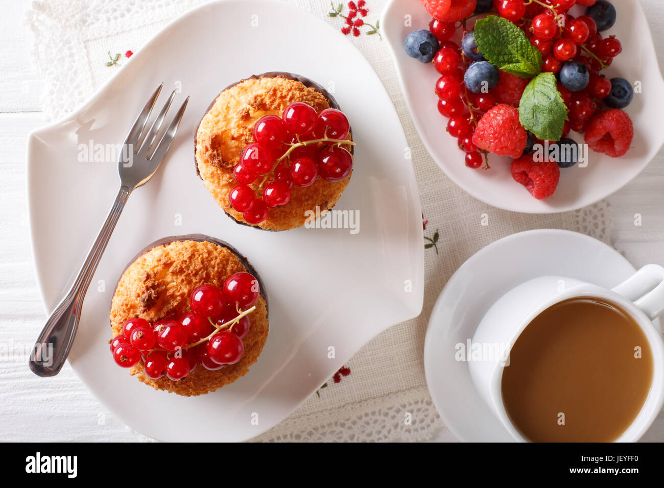 Delicious breakfast, coconut muffins, berries and coffee with milk close-up on the table. horizontal view from above - Stock Image